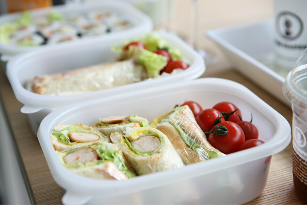 Container with a roll up sandwich and cherry tomatoes