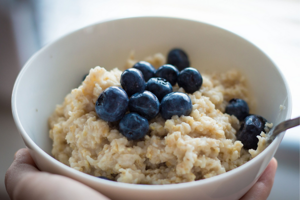 A bowl of oatmeal topped with blueberries