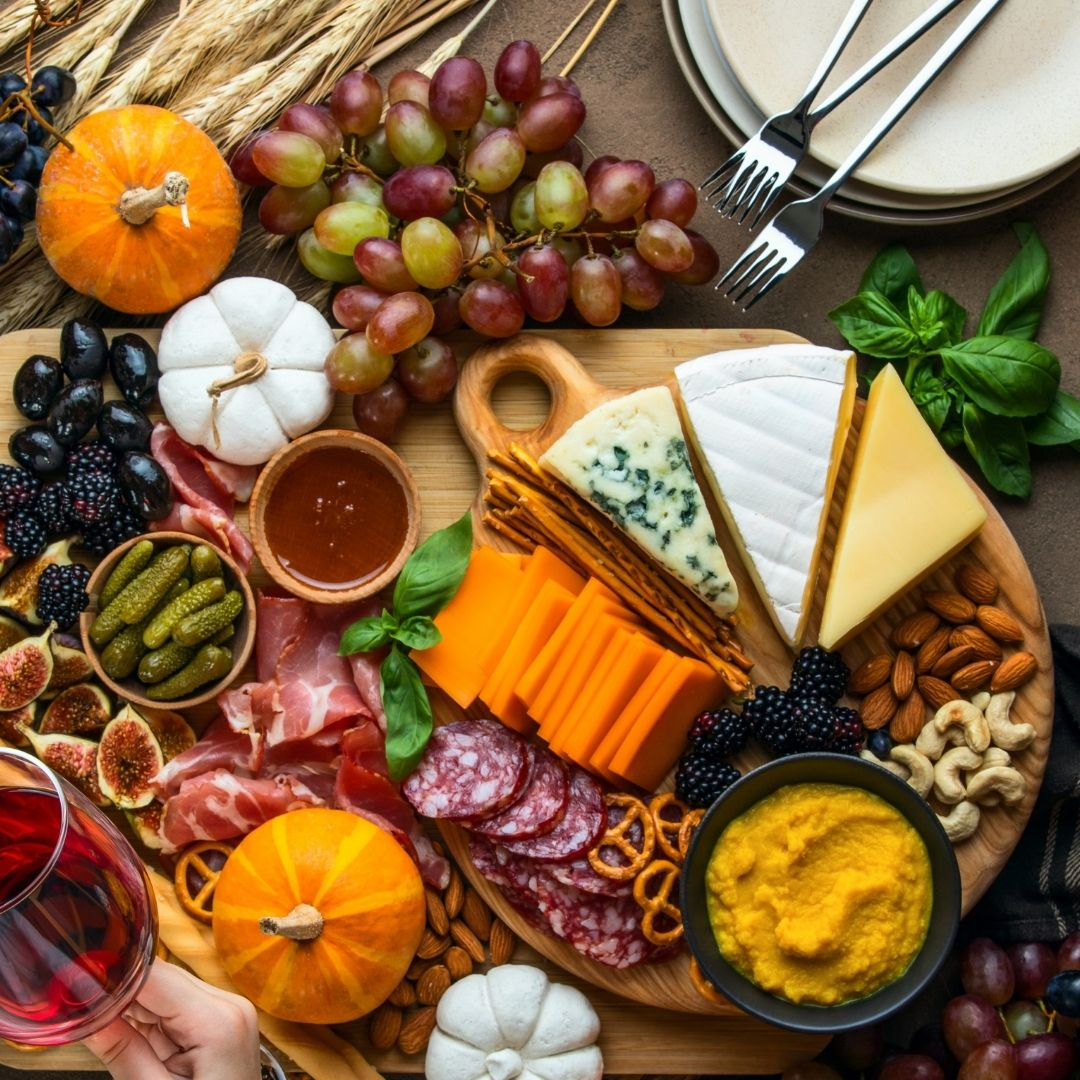 A snack board with an assortment of cheese, meats, fruit, vegetables, and grains