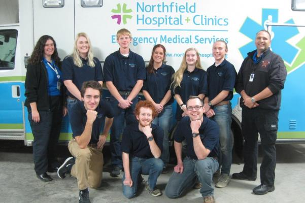 A class of students smiling in front of an ambulance