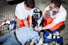 Two male EMS workers helping an injured patient