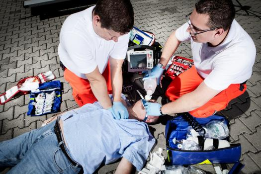 Two emergency medical technicians working on patient
