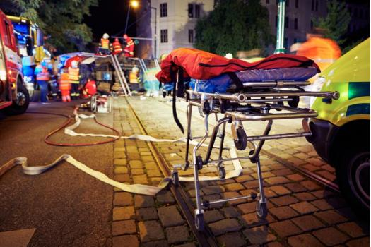 patient on gurney being wheeled into ambulance at night