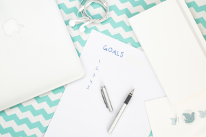 A goal worksheet next to a computer and planner