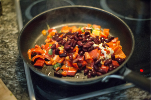 Peppers, beans, onions, and fish in a skillet