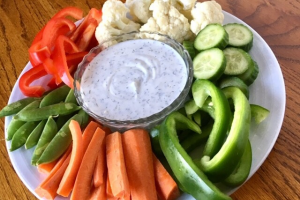 A bowl of greek yogurt dill dip surrounded by fresh veggies on a platter