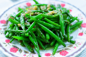 A plate of green beans topped with toasted almonds